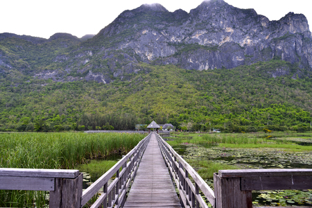 Old wooden bridge path to pavilion on lagoon and big mountains background.