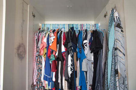 untidy: untidy and messy of women clothes in closet white wardrobe Stock Photo