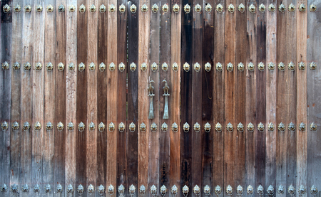 Beautiful old wooden door with iron knock ornaments and a couple of birds  metal handle Stock Photo