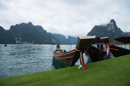Landscape mountains lake view and mist of boats droping at lake side at Khao Sok national park in Suratthani, Thailand
