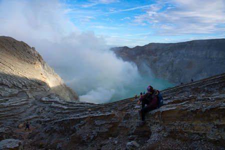 Woman sitting on top of crater Mount Kawah Ijen volcano is the largest sulfuric acidic lake in the world with smoke and fog,famous, popular and landmark travel destination in Java Island Indonesia.