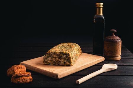 Photo of homemade Classic Bread Stuffing with chicken and balsamic on black background. Illuminated Chicken roll with pastry on wooden board. 写真素材