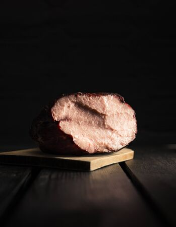 Close up dark photo of illuminated smoked ham on wooden board with black background.  Fresh sliced  smoked meat on wooden table (isolated shot). 版權商用圖片