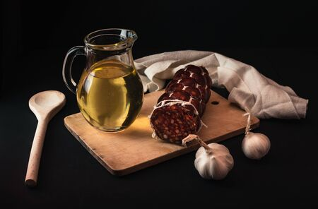photo of salami, garlic, oil and wooden board on black background. Traditional Slovak cuisine on dark background with decor. Stock Photo