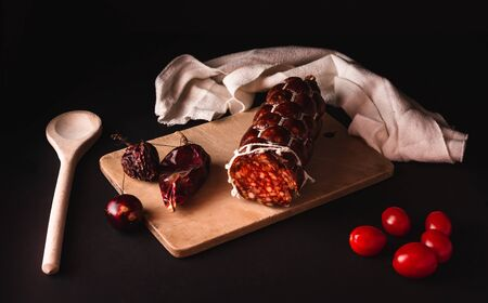 Photo of ladle, tomatoes and dried chilli on black background. Dark food photo of beef salami with cherry tomatoes and chilli with decor on wooden table