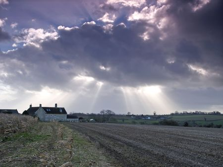 Landscape shot of a rural cottage in a harvested field with the sun breaking through overhead photo