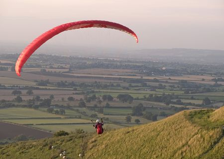 paraglide: Paraglider flying over the countryside Stock Photo