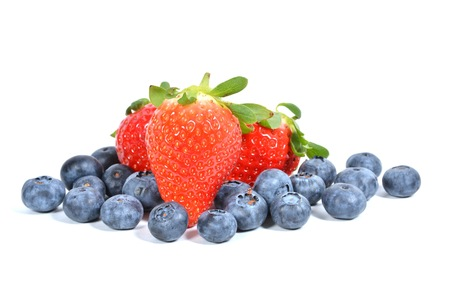 Pile of blueberries and strawberries isolated on white.