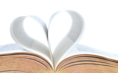 Close crop of a bible with pages making a heart. Isolated on white.