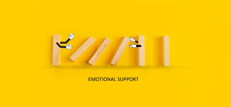 Emotional support concept. Bully pushed a domino with another holding arms open for emotional support. Banque d'images