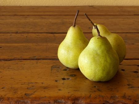 three mature pears on old wood table