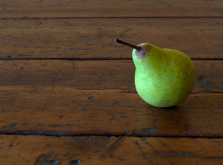 one pear on old antique wood table photo