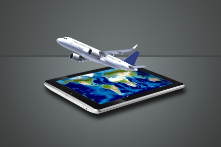 Plane flying out of digital tablet posed on grey feathered background photo