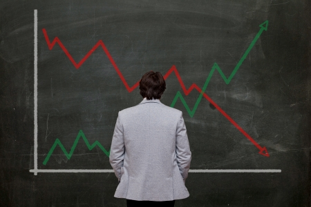 man looking at graph on blackboard, rear view Stock Photo - 16556584