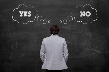 businessman think about yes or no in front of blackboard