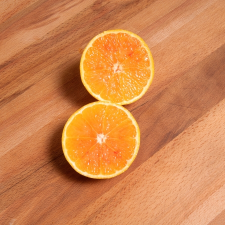 orange sliced in two parts on wood table