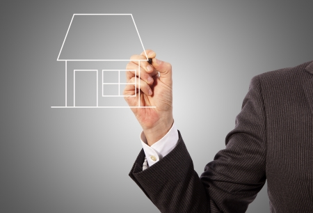 Male hand drawing a house on glass board, grey background Stock Photo