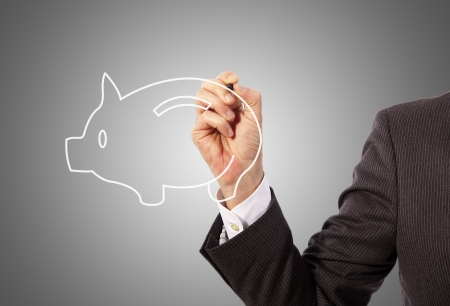 Male hand drawing a piggy bank, grey background Stock Photo - 17961814