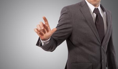 business man touching virtual screen, grey background Stock Photo