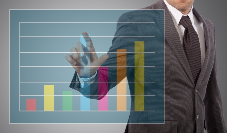 business man touching graph on screen, grey background Stock Photo - 17961873