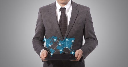 edu: business man with touch tablet in hands, grey background  world map from www lib utexas edu Stock Photo