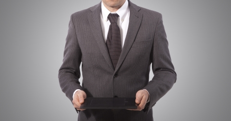 business man with touch tablet in hands, grey background