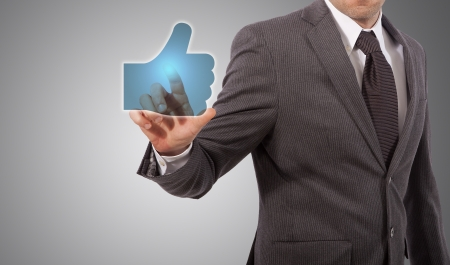 Businessman Presses a Like Button, grey background Stock Photo - 18650107