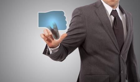 expressing negativity: Businessman Presses a dislike Button, grey background Stock Photo