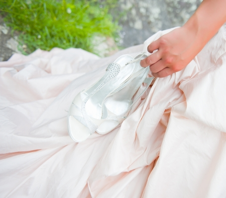 bride handling her shoes Stock Photo