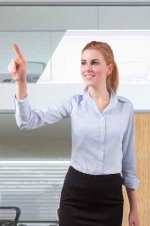 Young beautiful businesswoman pointing at copyspace