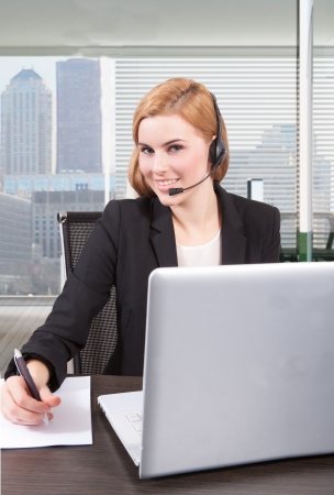 Businesswoman sit at desk and talking on headset  photo