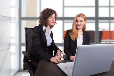 two businesswoman working in office at laptop
