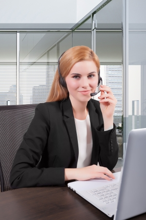 Businesswoman sit at desk and talking on headset  Stock Photo