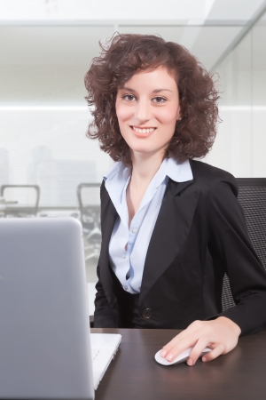 A woman sits at a desk in front of a computer screen.