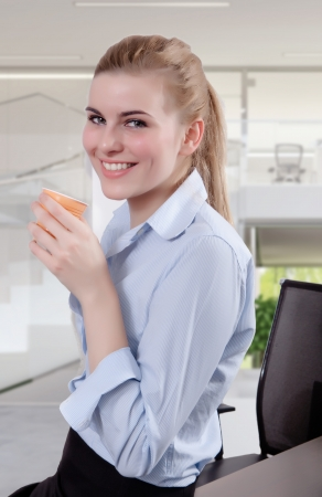 Successful business woman looking in the camera with a cup of coffee in her hand. Copy space.  Stock Photo