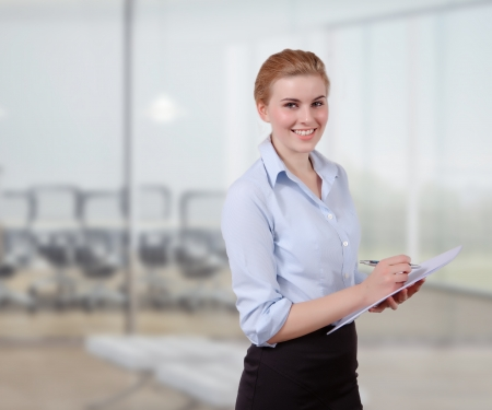 Young Businesswoman with Folio in her office