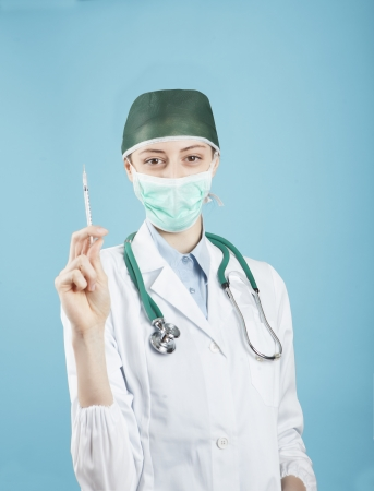 Doctor holding medical injection syringe and stethoscope