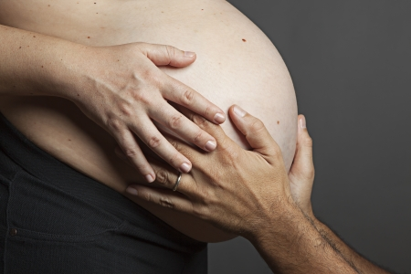Mother and Father gently hold the pregnant belly photo