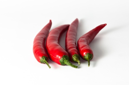 intense flavor: four chili peppers with stems on a white background.