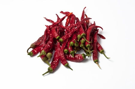 dehydrate: Several dehydrate cayenne peppers and stems on a white background. Stock Photo