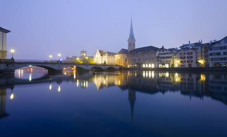 View of Zurich and old city center reflecting in the river Limmat at night. photo