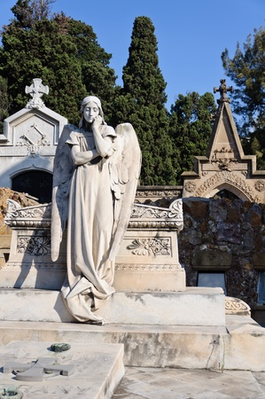 Tomb decorated with statues and sculptures in the monumental cemetery of Montjuic - Barcelona, Spain