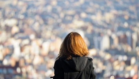 facing backwards: Girl facing backwards observing a city  The city is distant and out of focus  Stock Photo