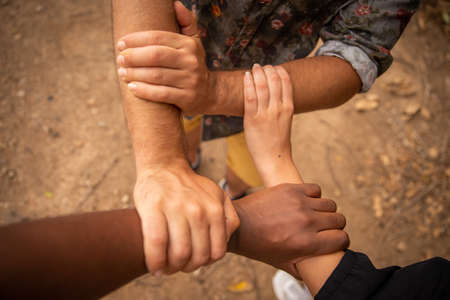Hands of different color to fight racism. 4 hands touch and form a multicolored square. Interracial hands Banque d'images