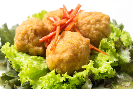 balls deep: Deep fried shrimp balls, garnished with sliced red chili, red oak and green lettuce. Ingredients--shrimp meat, pork fat, pepper, salt, sugar. Deep fried with palm oil Stock Photo
