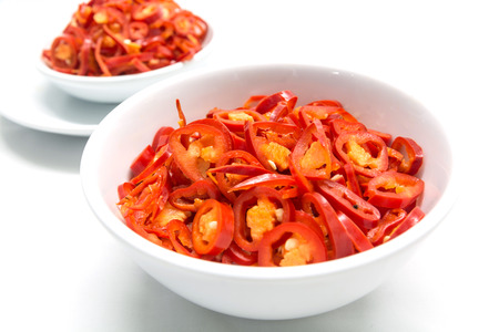 fat burning: Burning fat by eating hot chil, Sliced red chili in white ceramic bowl