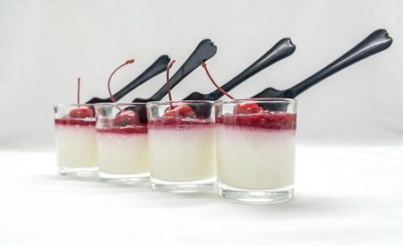 embouteillages: yogurt penna cotta with red cherry and berry jams in glassware and spoon on white tone background Banque d'images