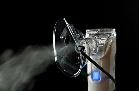 An electronic inhaler for inhaling medication against a black background