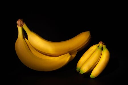 Big and small bananas on black background
