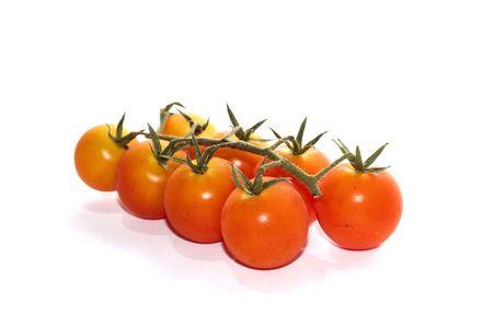 Cheery tomatos still on part of vine isolated on white Stock Photo